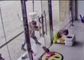 店铺内小猫遭过路男孩虐打 用门店的玻璃门夹住小猫头